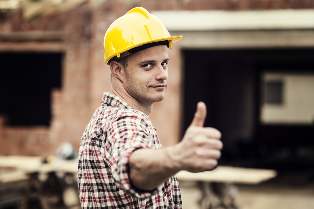 Foto van vakman met helm op die zijn duim opsteekt