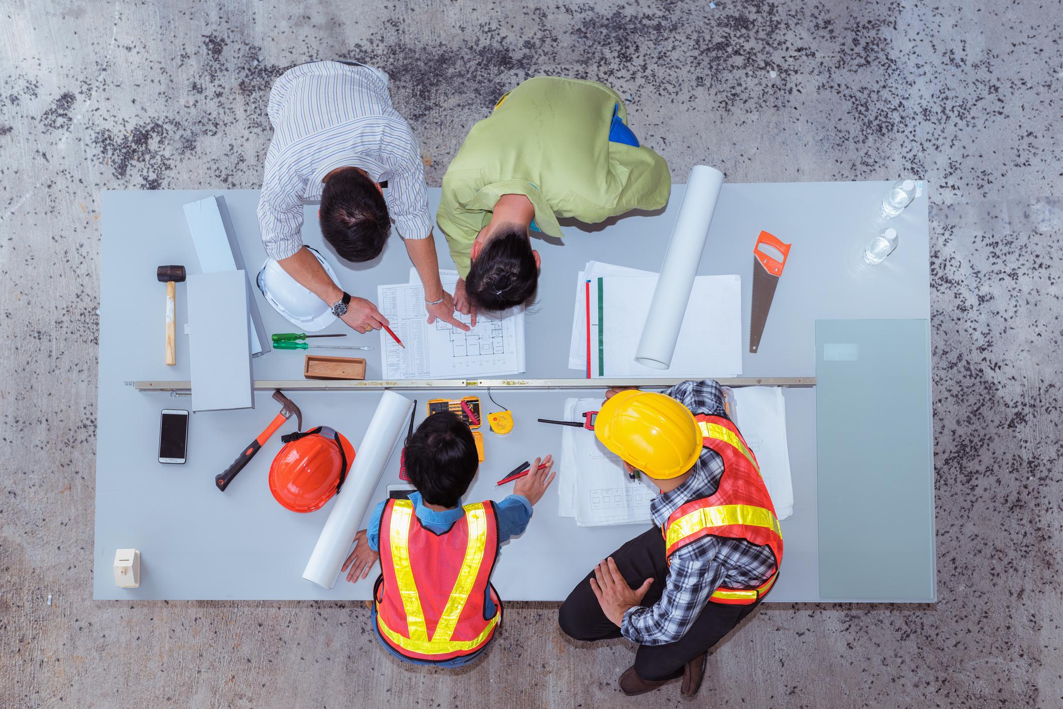 Bovenaanzicht van 4 mensen uit de bouwsector die plannen bespreken